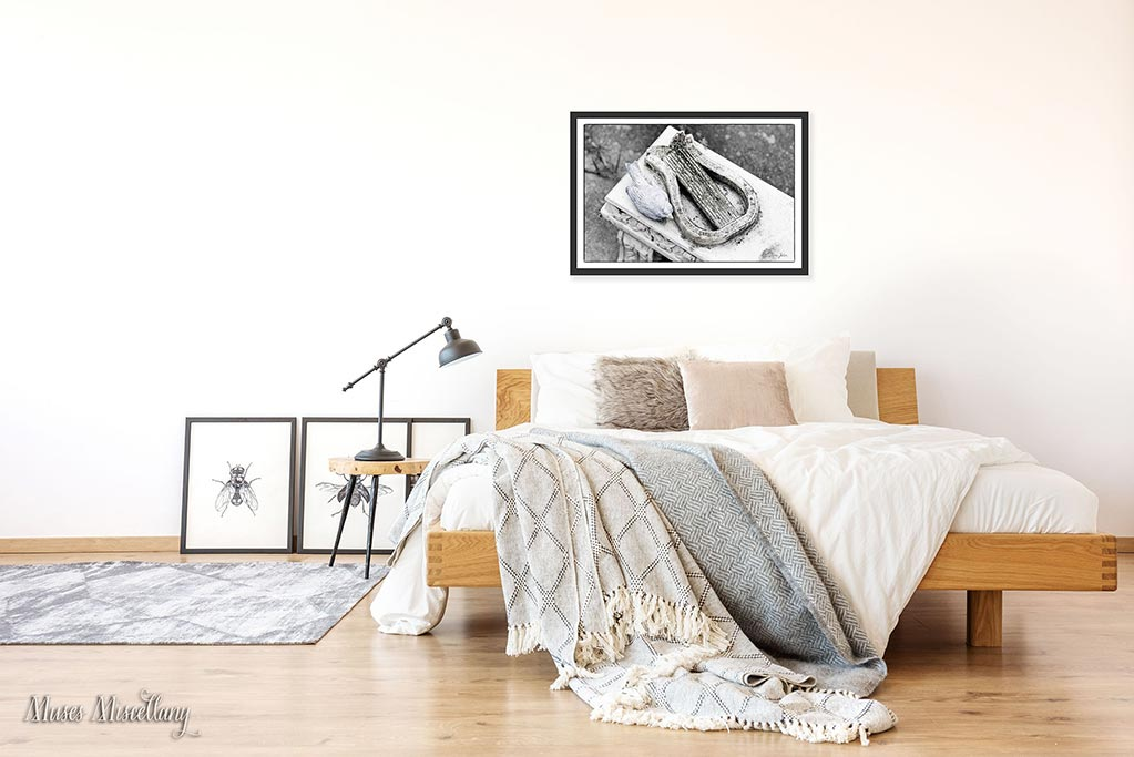 "Mockup of a 36x24"" ""Bluebird of Happiness"" poster in a black frame hanging over a contemporary-style bed. The room is bright and airy, with accents of light wood, grays, tans, and black."