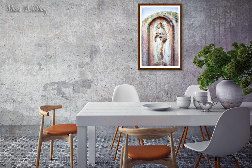 """Mockup of a 24x36"""" poster of """"Cherished"""" framed in dark wood, hanging in a dining room on a distressed gray wall. Colors in the print echo the retro chairs' orange seats and greenery in a white planter."""