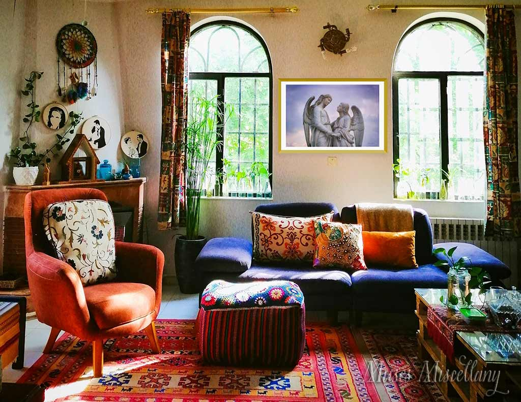 """Mockup of a 36""""x24"""" poster of """"Comfort"""" in a gold frame, hanging in a Bohemian living room. The room's prominent purple, pink, and orange hues work well with the print's colors."""