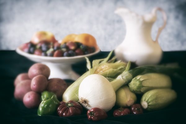 Still life photo of fruits and vegetables in a soft, muted vintage style.