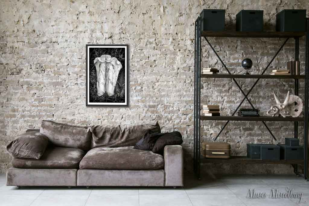"""Mockup of a 24x36"""" poster of """"Feet Last"""" in a black frame, hanging on a brick wall over a taupe velvet couch. To the right, tall black shelves house a collection of books, black boxes, and quirky vintage items."""
