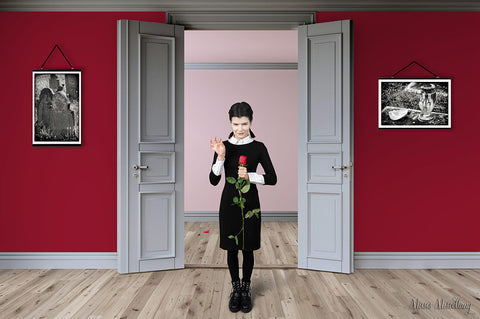 Two Gothic black and white posters hang in a red room, one on each side of a doorway where a woman dressed like Wednesday Addams plucks a petal from a rose. Image of woman in room from Icons8.com.