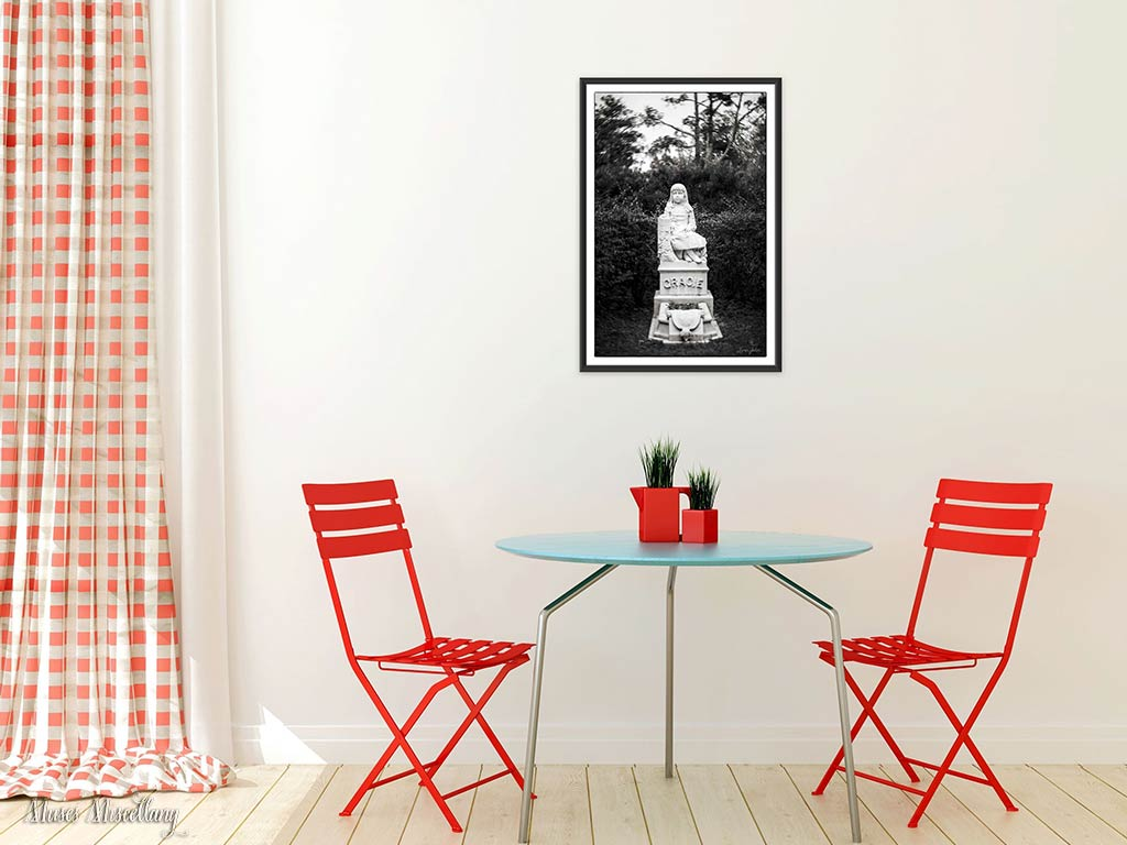 "Mockup of a 24x36"" poster of ""Gracie"" in a black frame. It hangs on a white wall by a bistro set with red slat chairs and a round table with light blue top and silver legs. To the left, a white and red gingham curtain covers a tall window or door, pooling on the light wood floor."