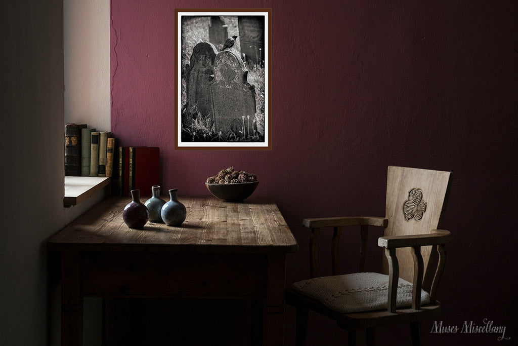 """Mockup of a 24x36"""" poster of """"Harbinger"""" in a mahogany frame on a maroon wall, hanging over a dark wooden desk."""