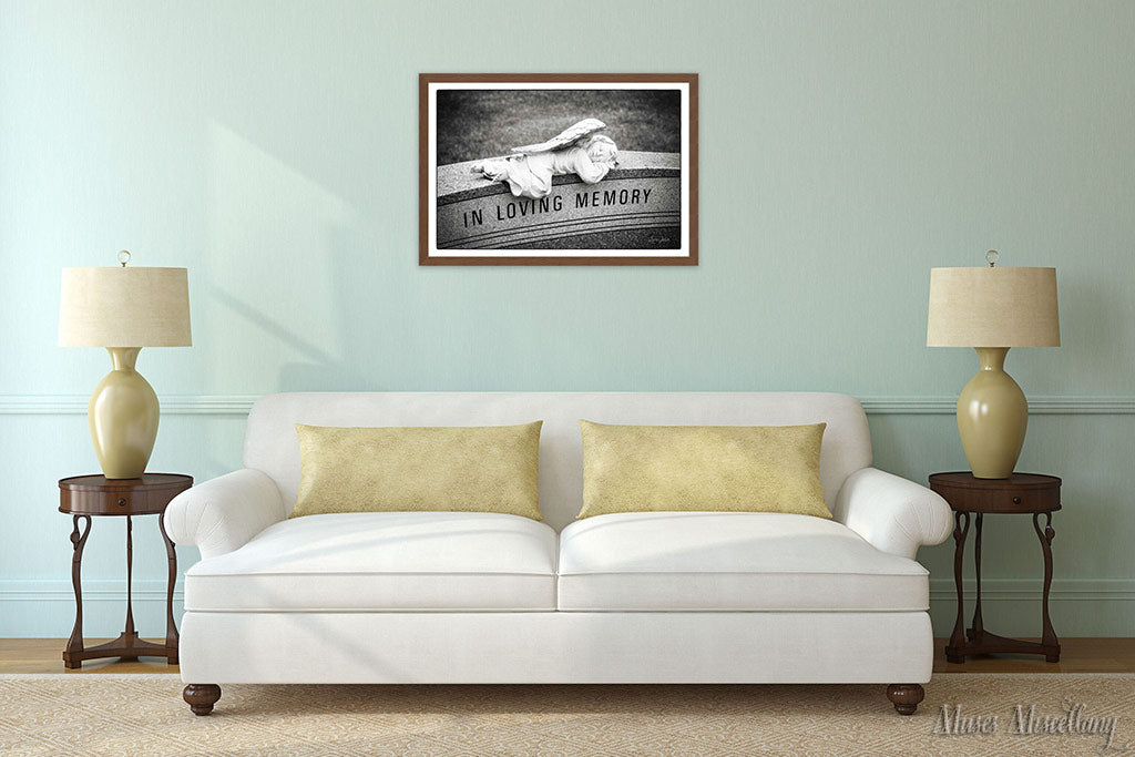 """Mockup of a 36x24"""" poster of """"In Loving Memory"""" in a walnut frame, hanging over a white sofa in a vintage living room. Antique walnut end tables flank the sofa. Pale green walls and mustard accents give the room a tranquil, cheerful feel."""