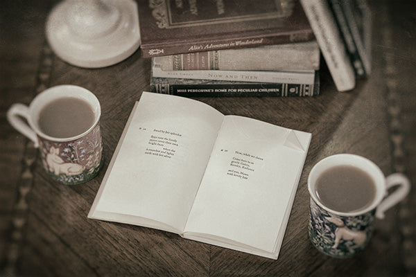Vintage-style still life photo of an open book on a coffee table, with a cup of tea on each side and a stack of books behind.
