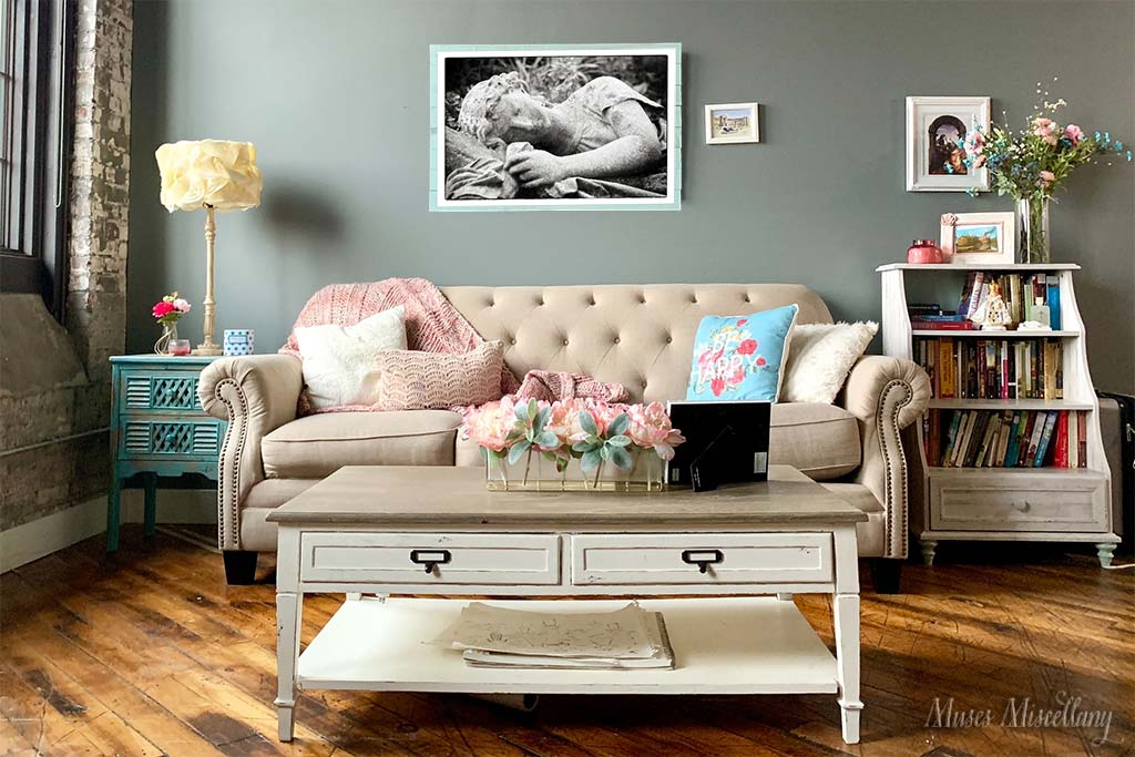 """Mockup of a 36x24"""" poster of """"Sleeping Beauty,"""" mounted on aqua-painted wooden boards. It hangs in a romantic, shabby chic living room full of color, particularly light blues, pinks, and aquas."""