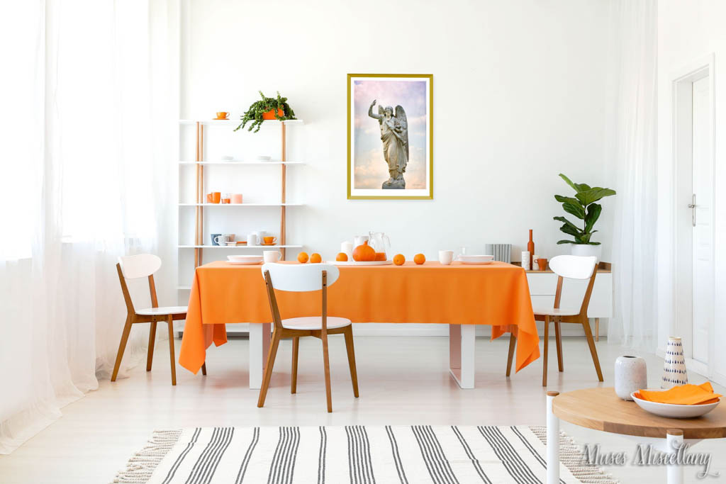 """Mockup of a 20x30"""" poster of """"Transcendence"""" in a gold frame. It hangs in a sunny, white dining room decorated in a contemporary style with retro chairs. An orange tablecloth and accessories add a pop of fun, while wood accents and plants add a natural touch."""