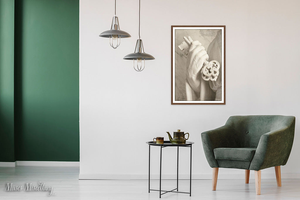 "Mockup of a 24x36"" poster of ""You Hold the Keys"" in a walnut frame, hanging on a white wall by a green velvet chair and a small, round metal table topped with a ceramic teapot and mug. Sleek, silver pendant lamps and a forest green accent wall add interest."