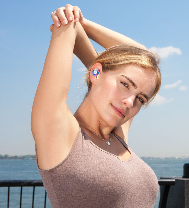 attractive blond women using the true wireless earbuds raycon E70 pro in light blue