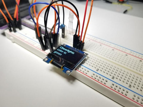 Breadboard circuit containing OLED screen displaying data from Cheerlights feed