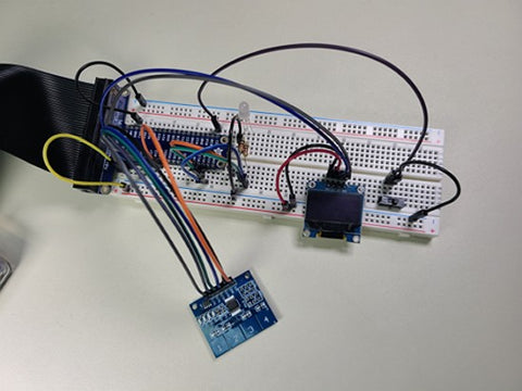 Breadboard circuit with capacitive touch sensor and OLED screen