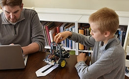 Man and Boy working on robot