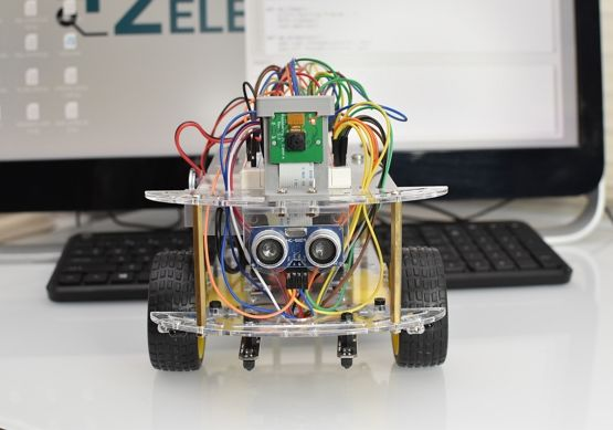 Robot sitting on desk in front of computer monitor