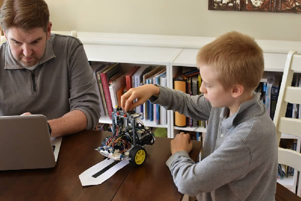 Man and boy building line following robot using Python code