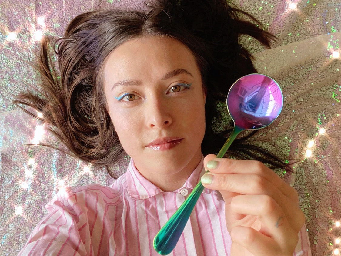 Umeko Motoyoshi holding an Umeshiso rainbow cupping spoon against a sparkling sequin background