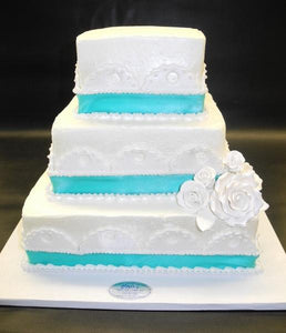 White Icing Wedding Cake with Fondant Decorations and Blue Ribbon