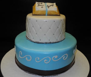 Religious blue, white, and brown cake with edible bible on top