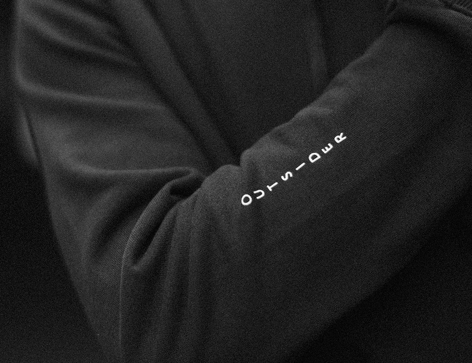 Upclose of lettering on the forearm of the Outsiders sweater.