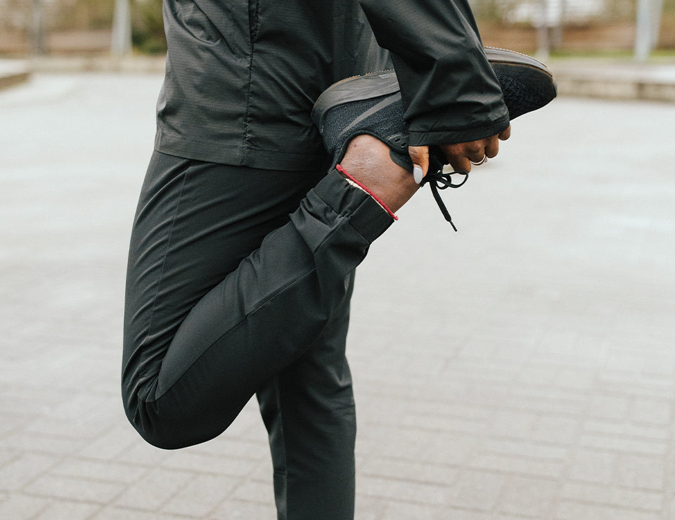 A woman stretching her quadricep in the destination pant.