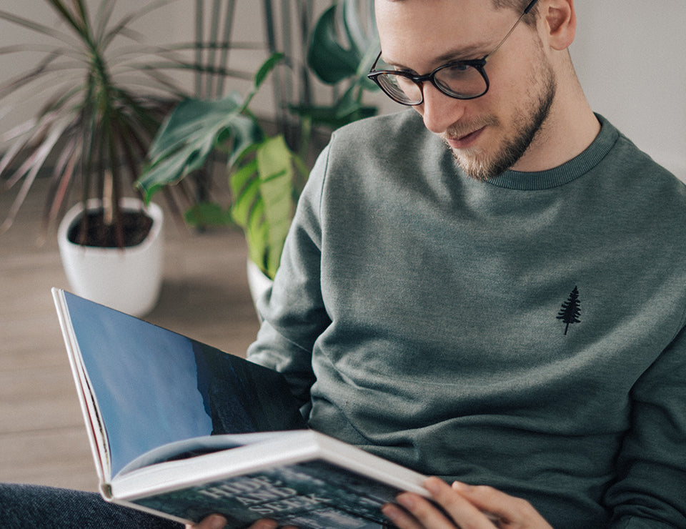 A man reading a book in a green tentree golden spruce crewneck sweatshirt