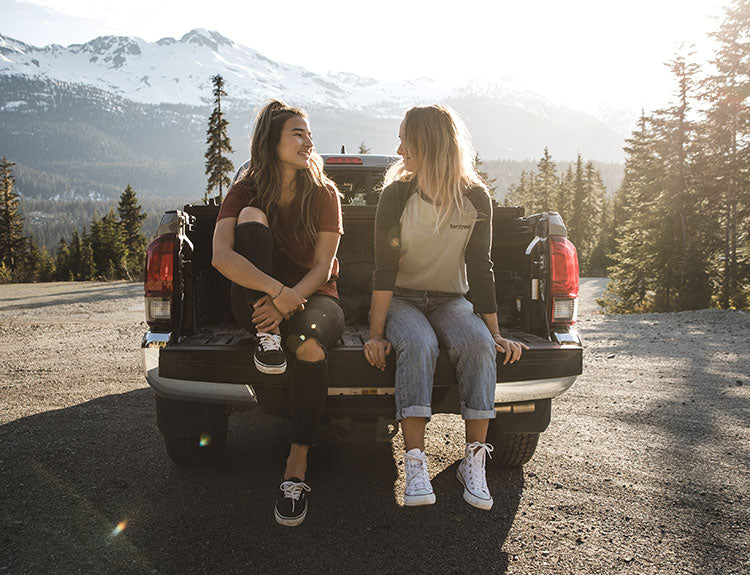 Image of two girls sitting on the tailgate of a truck smiling at each other.