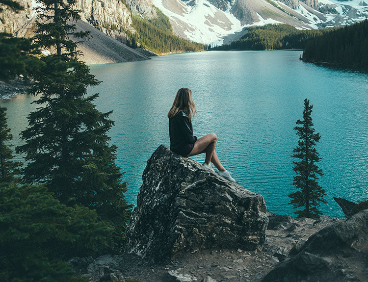 Image of a woman sitting on a rock overlooking a lake and mountains with snow