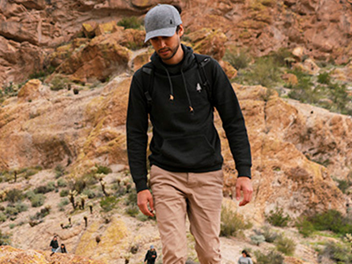 A man wearing tentree apparel hiking in an arid climate.