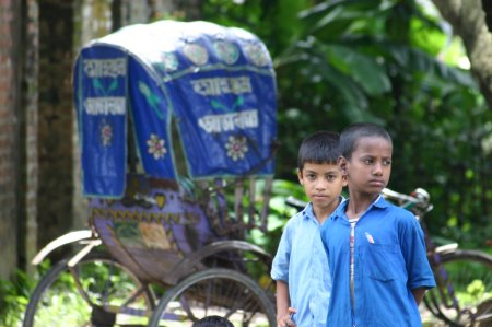 Australian Cricket Tours - Two Young School Boys Standing On A Railway Platform, In Front Of A Blue Canvassed Bicycle Rickshaw. Of All Our Australian Cricket Tours To Bangladesh, This Stand As One Of My Favourite Cricket Tour Photos From Bangladesh