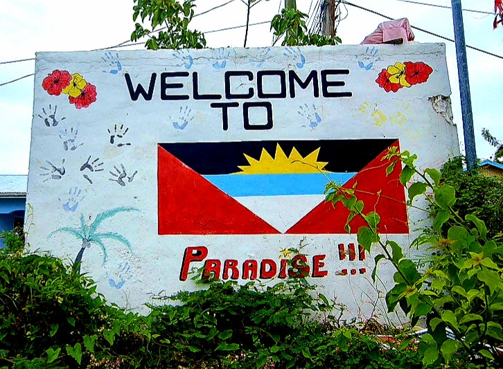 Australian Cricket Tours - Antiguan Flag Painted On A Wall With The Slogan 'Welcome To Paradise'