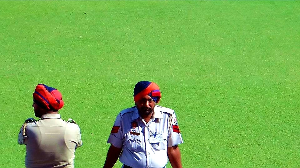Australian Cricket Tours - Two Police Officers 'Relax' Against The Railings With A Vast Green Grass Backdrop Of The Punjab Cricket Association Stadium, Mohali | India