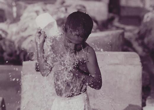Australian Cricket Tours - A Child Throws Water Over Himself In The Laundry Ghat | Karachi | Pakistan