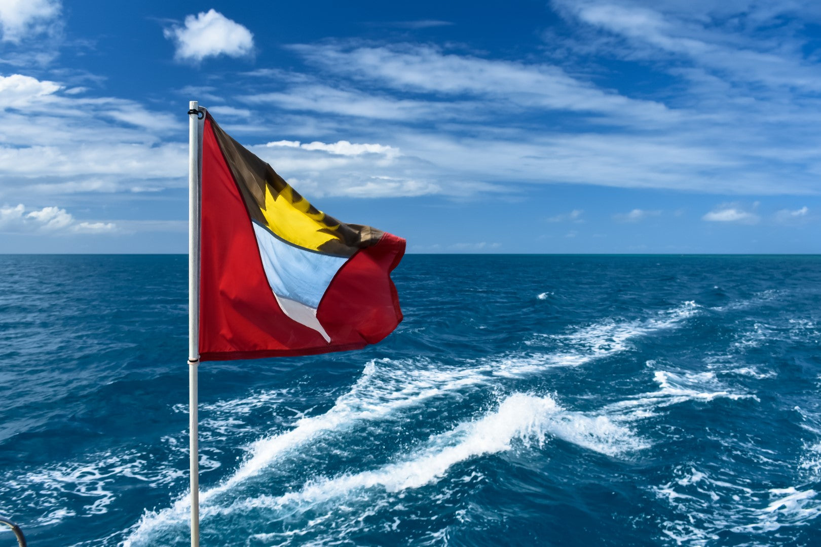 Australian Cricket Tours - Antiguan Flag Flowing Freely From The Stern Of A Wadadli Catamaran Sailing Around Antigua