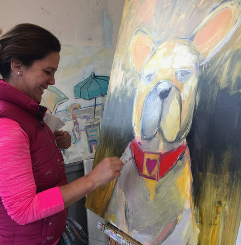 Artist Michelle Rivera at her easel painting a dog