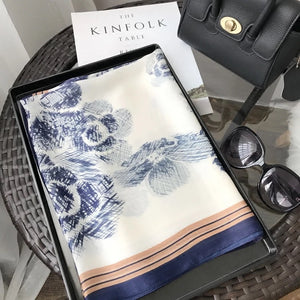 Blue and white floral print silk scarf with blue trim.