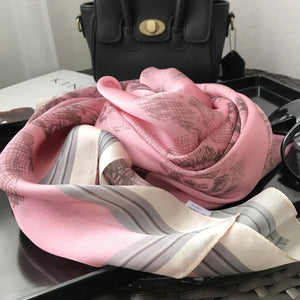 Pink and black floral print silk scarf with tan trim.