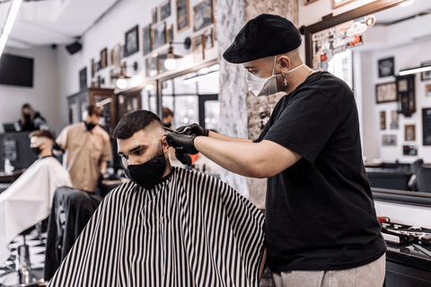 barber with mask cutting hair