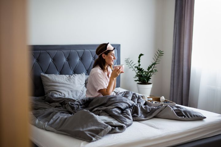 Woman drinking coffee while in bed.