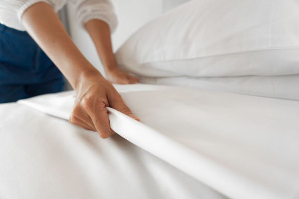 Woman making a bed with clean white bed sheets
