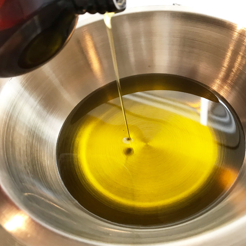 organic olive oil being poured into bowl