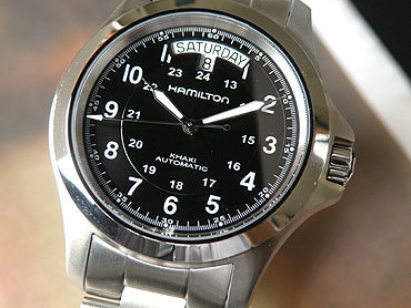 Hamilton Khaki King II has silver-tone stainless steel case w/bracelet. Black dial w/luminous hands & Arabic numeral hour markers. Scratch resistant sapphire crystal.