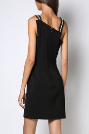 Little black dress with asymmetric neck and stripes of pearls