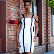 Little white sheath dress with two black pearly strap lines.