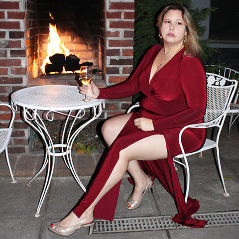 A woman wearing a red dress seated by the fire