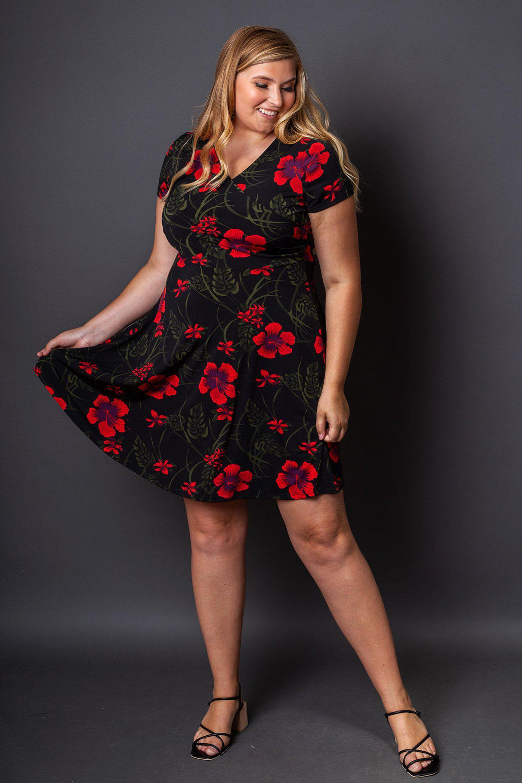 Holly Fit and Flare Floral Dress front view on model holding one side of the skirt