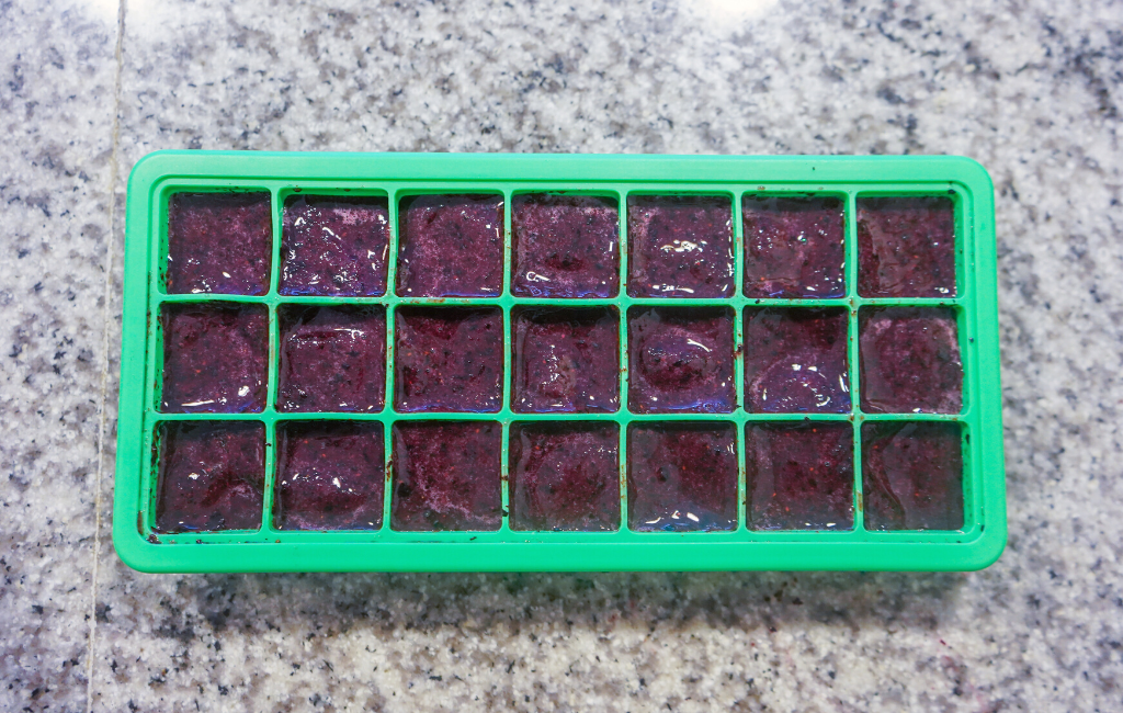 poured frozen blueberries in ice cube tray