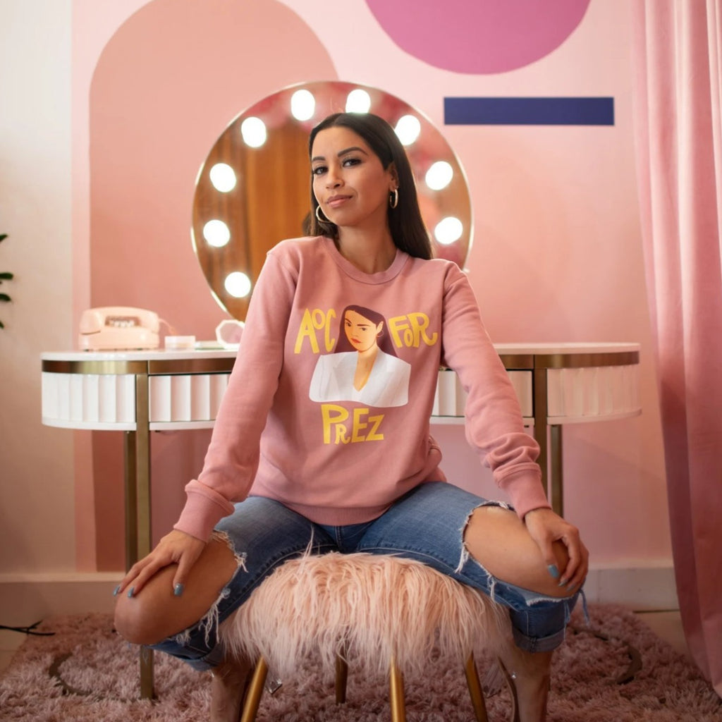 Model is wearing AOC for Prez unisex pink GRL Collective sweatshirt. 100% cotton and pre-shrunk. Model is wearing XS. Sizes are XS-2XL