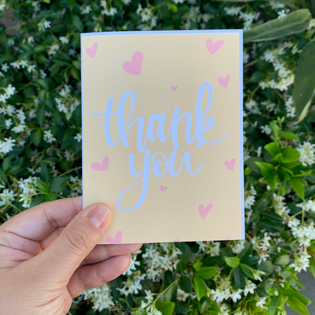 Yellow thank you card with pink hearts and white writing. Designed by Latina brand GRL Collective.