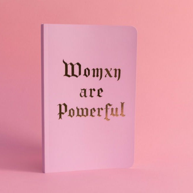 Womxn Are Powerful Lux Notebook is matted pink with gold foil lettering. Made from premium recycled paper. 8.25 inches x 5.25. 144 thick pages