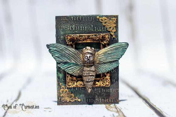 Wooden Tea light holder featuring a sculpted death head hawk moth with swarovski crystals for eyes. The candle holder is made from wood and embossed with gothic lettering. The base is a dark metallic green with rusty orange highlights. The moth is mounted onto a golden frame on the front of the wooden pillar candle holder and two opposite corners have metal corner accent pieces also in gold. The top of the candle holder has a metal dish for the tea light candle to sit in.